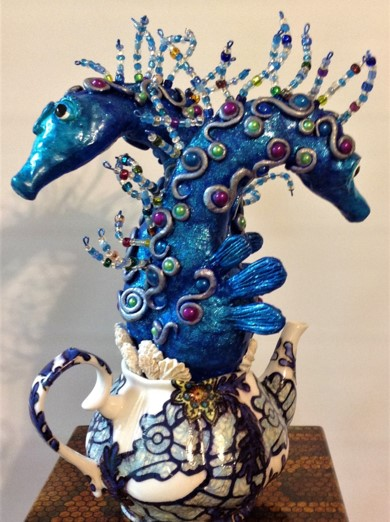 Two blue sea horse sculptures emerging from a tea pot
